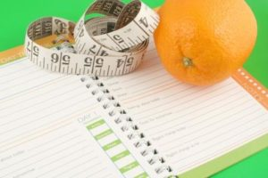 A Notepad, an Orange and a Measuring Tape on a Green Background