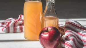Bottles of apple cider vinegar and an apple
